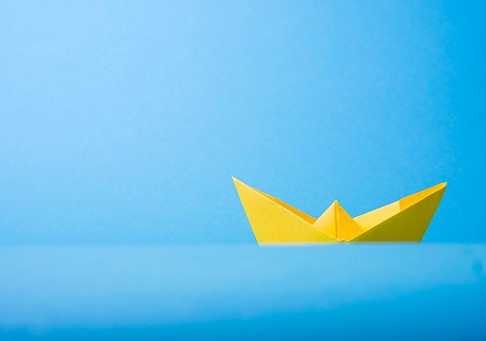 Barco de papel sobre fondo azul