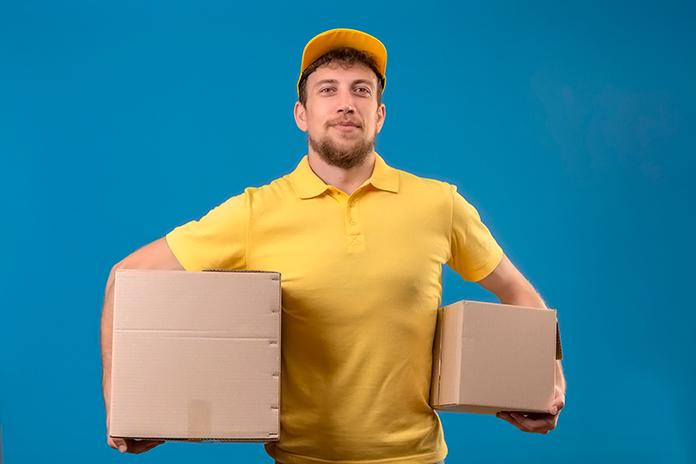 Repartidor sujetando dos cajas con ambos brazos
