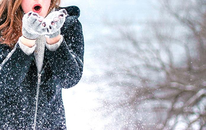 Mujer abrigada jugando con la nieve