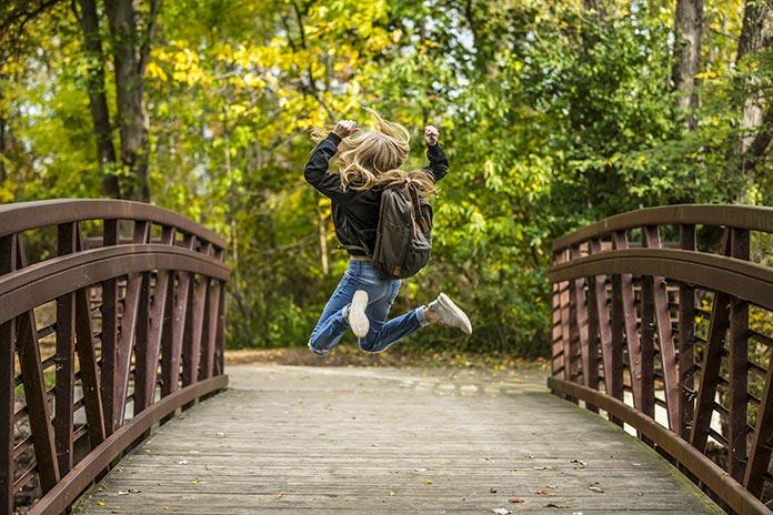 Niña saltando en un puente
