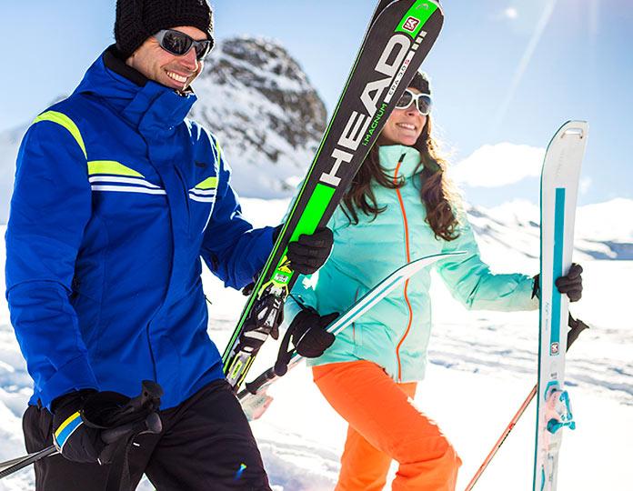 Pareja con esquís en la mano caminando por la nieve