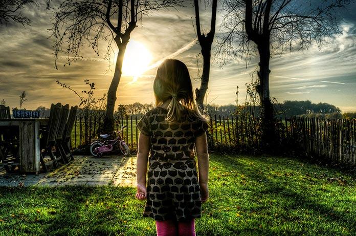 Niña mirando de frente al sol