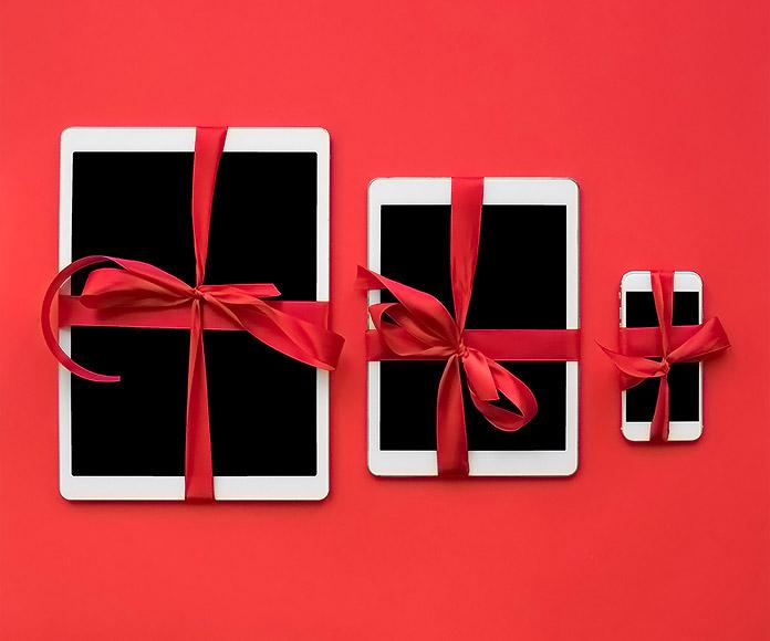 tables y smartphone adornados con un lazo de regalo