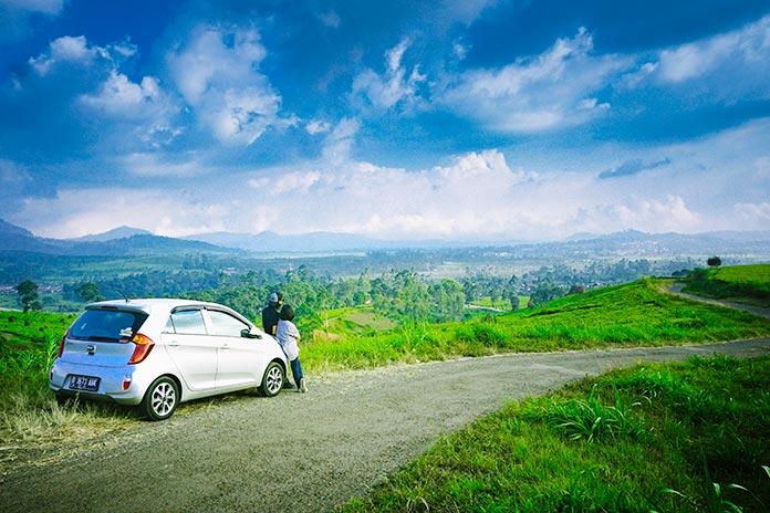 personas viendo el paisaje sentadas sobre el capó del coche
