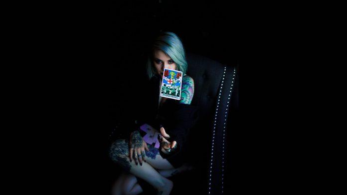 mujer tatuada lanzando una carta de tarot
