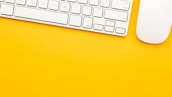 teclado y ratón sobre un escritorio amarillo