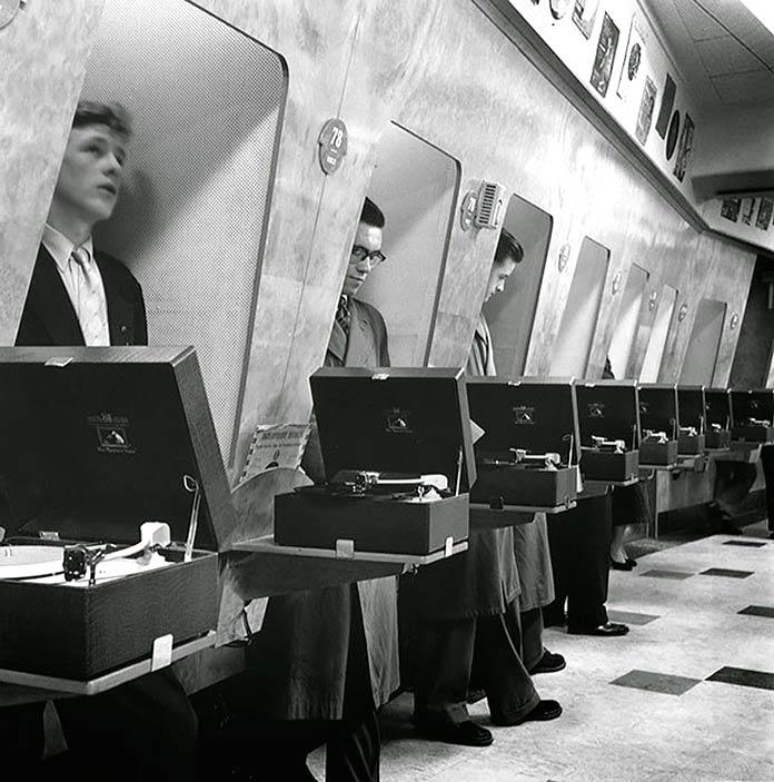 Clientes escuchando música en una tienda de discos. Londres, 1955