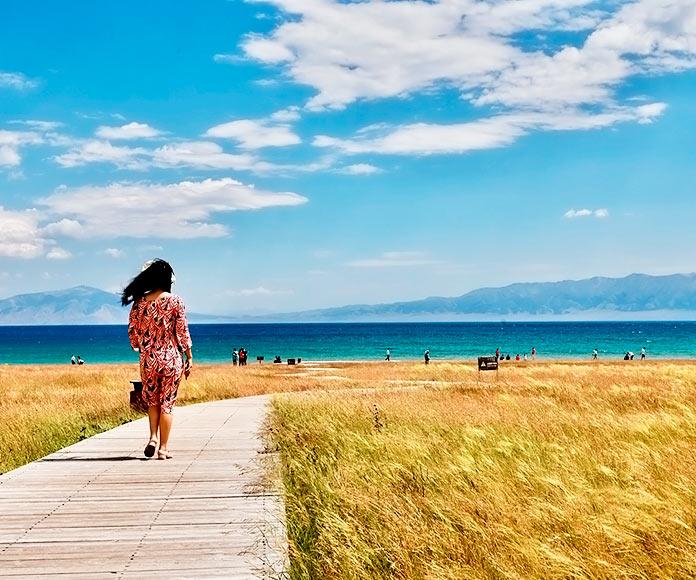 Mujer caminando por un paseo de madera en una playa de Europa