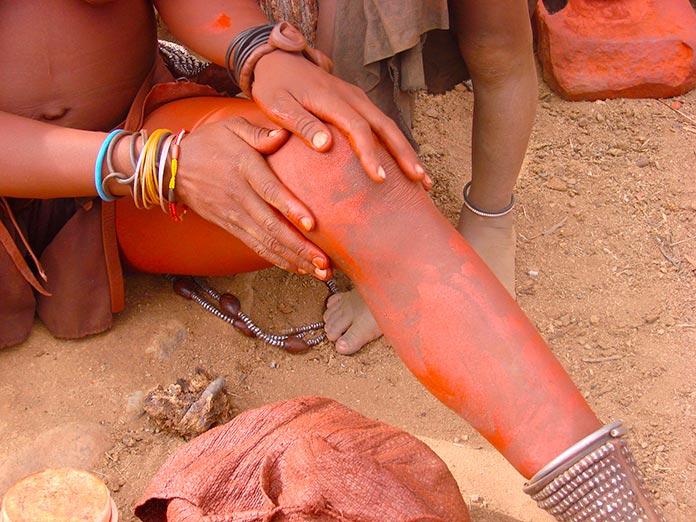 Mujer himba cubriéndose con el ungüento rojo