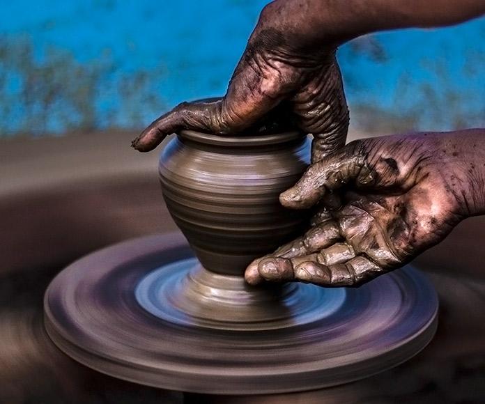 manos trabajando una vasija de barro en un torno de alfarería