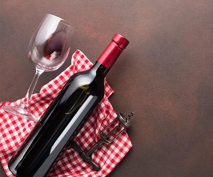 Botella y copa de vino sobre un mantel encima de una mesa