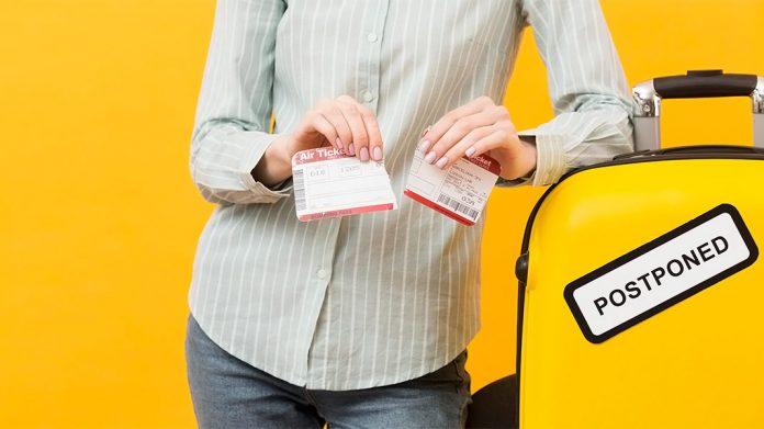 mujer rompiendo un billete de avión junto a una maleta con una pegatina que dice